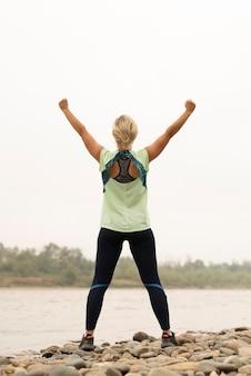 Foto completa de uma jovem mulher com os braços no ar