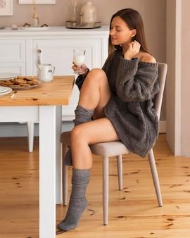 Foto completa de uma mulher aconchegante na cadeira segurando um copo de leite
