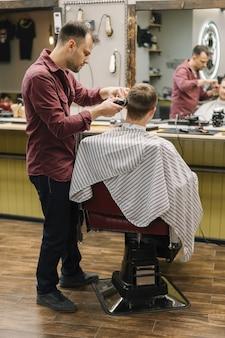 Foto completa do cabeleireiro dando um corte de cabelo