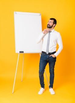 Foto completa do empresário dando uma apresentação no quadro branco, pensando em uma idéia enquanto olha para cima
