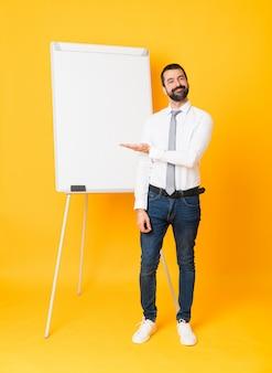 Foto completa do empresário dando uma apresentação no quadro branco sobre amarelo, apresentando uma idéia enquanto olha sorrindo para