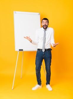 Foto completa do empresário dando uma apresentação no quadro branco sobre amarelo com expressão facial chocada