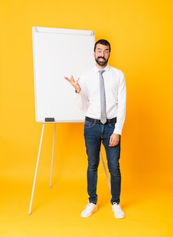 Foto completa do empresário dando uma apresentação no quadro branco sobre amarelo, fazendo o gesto de dúvidas