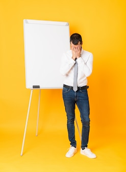 Foto completa do empresário dando uma apresentação no quadro branco sobre amarelo isolado com expressão cansada e doente
