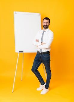 Foto completa do empresário dando uma apresentação no quadro branco sobre amarelo isolado com óculos e sorrindo
