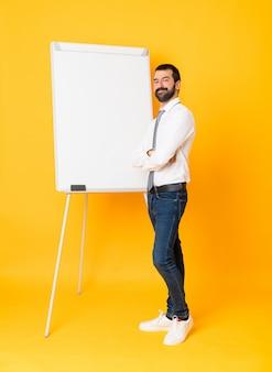 Foto completa do empresário dando uma apresentação no quadro branco sobre amarelo isolado com os braços cruzados e olhando para a frente