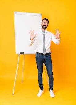 Foto completa do empresário dando uma apresentação no quadro branco sobre amarelo isolado, contando dez com os dedos