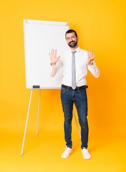 Foto completa do empresário dando uma apresentação no quadro branco sobre amarelo isolado, contando nove com os dedos