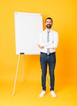 Foto completa do empresário dando uma apresentação no quadro branco sobre amarelo isolado, mantendo os braços cruzados na posição frontal