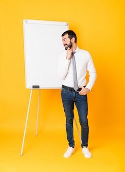 Foto completa do empresário dando uma apresentação no quadro branco sobre amarelo isolado, olhando para o lado