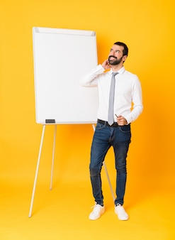 Foto completa do empresário dando uma apresentação no quadro branco sobre amarelo isolado, pensando uma idéia