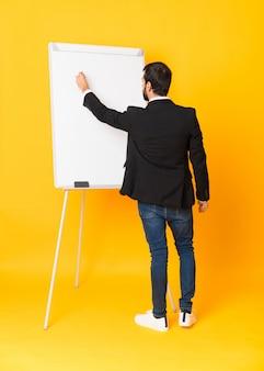 Foto completa do empresário dando uma apresentação no quadro branco sobre amarelo isolado
