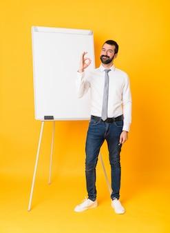 Foto completa do empresário dando uma apresentação no quadro branco sobre amarelo mostrando sinal okey com os dedos
