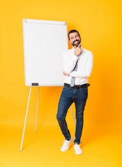 Foto completa do empresário dando uma apresentação no quadro branco sobre amarelo sorrindo