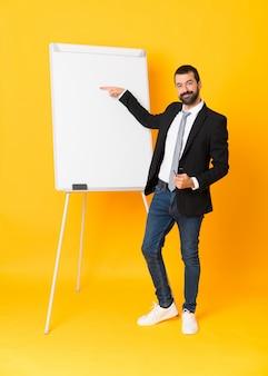 Foto completa do empresário dando uma apresentação no quadro branco sobre amarelo