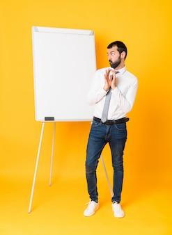 Foto completa do empresário dando uma apresentação no quadro branco sobre fundo amarelo isolado, planejando algo