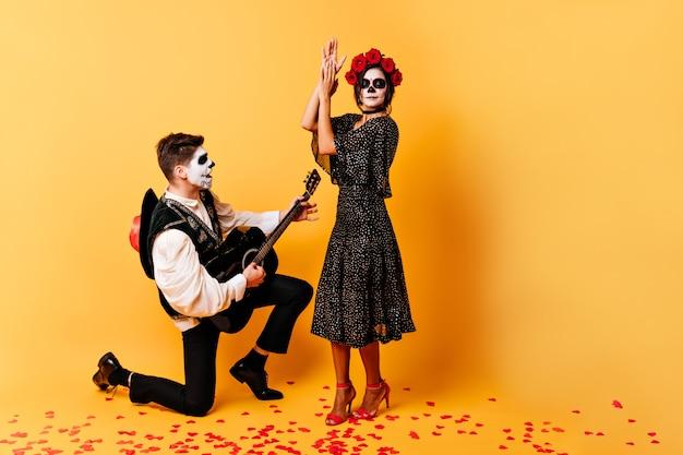 Foto completa do extraordinário casal criativo dançando e cantando na parede laranja. menina e menino com máscaras de caveira posando