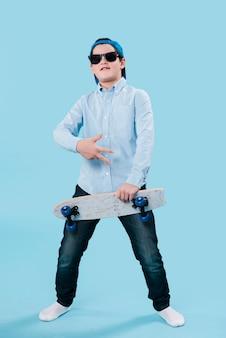Foto completa do garoto moderno com óculos de sol e skate
