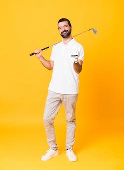 Foto completa do homem sobre fundo amarelo isolado jogando golfe e fazendo o gesto que vem