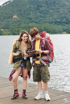 Foto completa do jovem casal asiático com mochilas em pé no cais e planejando sua rota no tablet pc