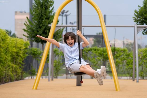 Foto completa garoto feliz no balanço