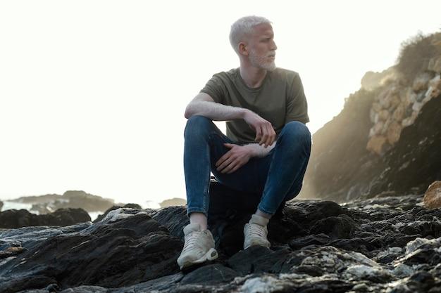 Foto completa homem sênior sentado nas pedras