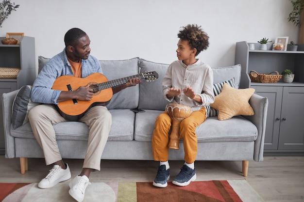 Foto completa horizontal de um homem afro-americano e seu filho passando um tempo juntos em casa tocando violão e djembê