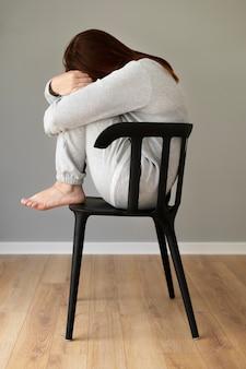 Foto completa mulher deprimida sentada na cadeira