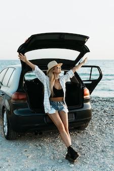 Foto completa mulher feliz parada no porta-malas do carro com uma garrafa de suco