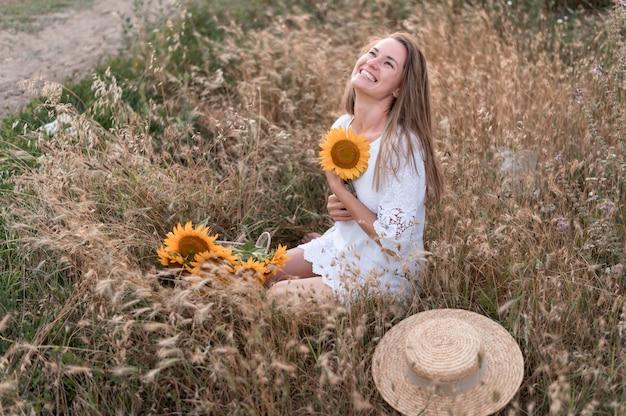 Foto completa mulher feliz segurando girassol