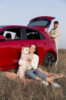 Foto completa mulher feliz segurando um cachorro fofo