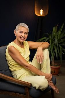 Foto completa mulher feliz sentada na cadeira