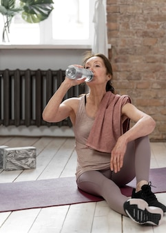 Foto completa mulher idosa bebendo água