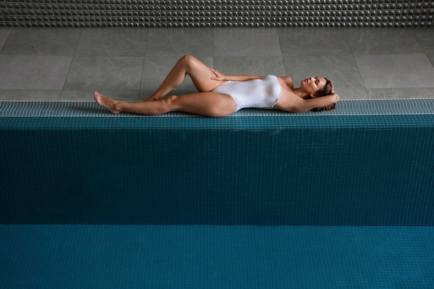 Foto completa mulher relaxada deitada perto da piscina