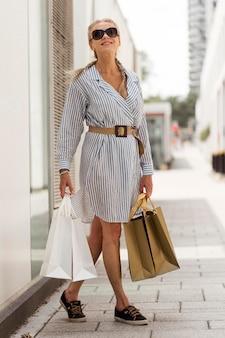 Foto completa mulher sênior carregando sacolas