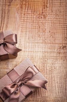 Foto conceitual de copyspace duas caixas de presente de papel pardo com fitas em uma placa de madeira vintage