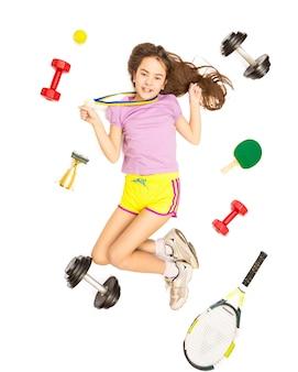 Foto conceitual de garota feliz com medalha de ouro posando com equipamentos esportivos