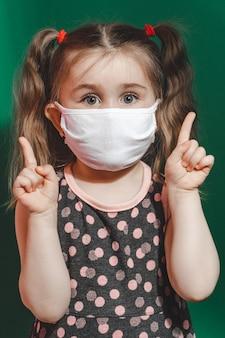 Foto conceitual de menina com máscara médica mostrando o dedo apontando sobre fundo verde perto de 2020