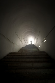 Foto conceitual de pessoa em pé no final do túnel diante do feixe de luz com as mãos levantadas