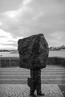 Foto conceitual em escala de cinza vertical de uma pessoa com cabeça de rocha carregando uma bolsa - conceito de departamento