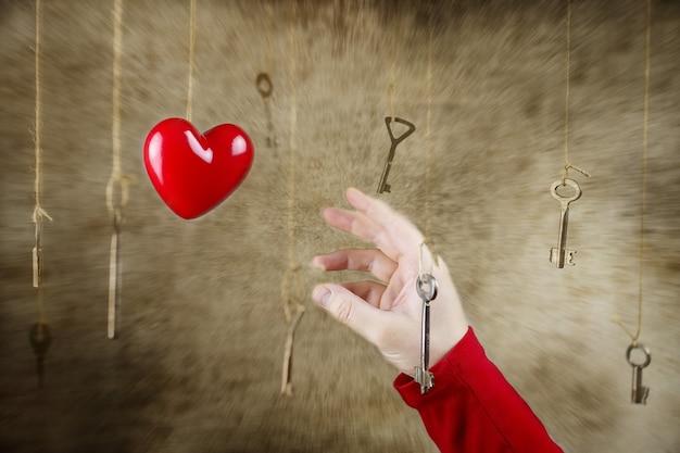 Foto conceitual estendendo a mão para uma das muitas chaves vintage penduradas em fios