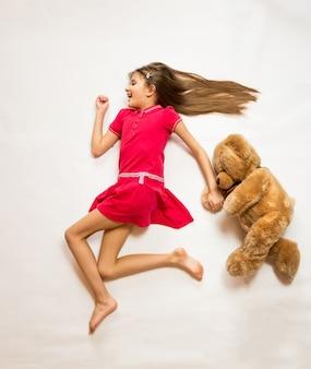 Foto conceitual isolada de linda garota feliz correndo com o ursinho de pelúcia
