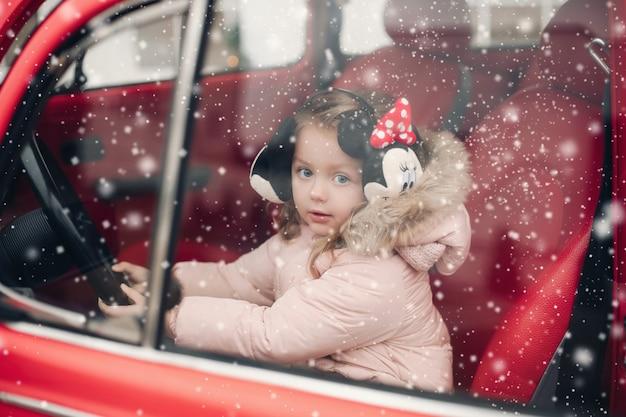Foto conservada em estoque da adorável garotinha em protetores de ouvido mickey e casaco de inverno, sentado no banco do motorista no carro vermelho. ela está olhando para a câmera pela janela sob a neve.