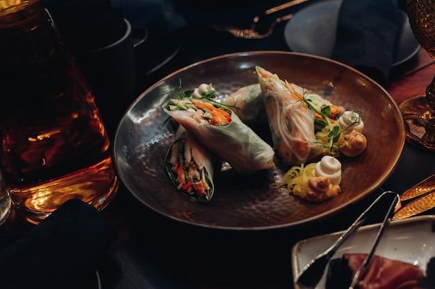 Foto conservada em estoque de comida contemporânea servida no prato da moda no restaurante. rolos de vegetais saudáveis com molhos servidos no prato.