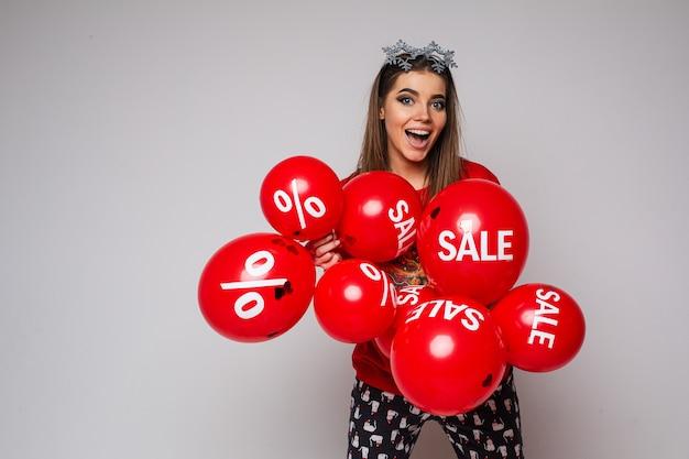 Foto conservada em estoque de mulher morena animada, de pijama, usando óculos extravagantes de floco de neve na cabeça e segurando um monte de balões de ar vermelho com adesivos de venda e desconto.