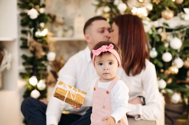 Foto conservada em estoque de um encantador vestido rosa de menina segurando um presente de natal dourado