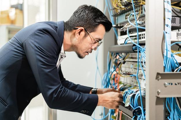 Foto conservada em estoque de um jovem técnico de rede segurando um tablet trabalhando para conectar cabos de rede no gabinete do servidor na sala do servidor de rede. engenheiro de ti trabalhando na sala do servidor de rede