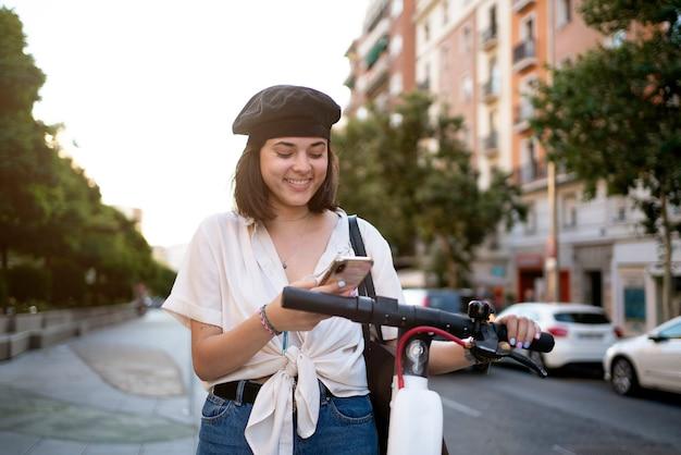 Foto conservada em estoque de uma bela mulher de cabelos curtos usando seu telefone na rua para desbloquear uma scooter pública. ela está sorrindo.