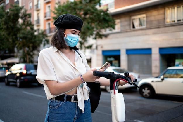 Foto conservada em estoque de uma bela mulher de cabelos curtos usando seu telefone na rua para desbloquear uma scooter pública. ela está usando uma máscara para se proteger.