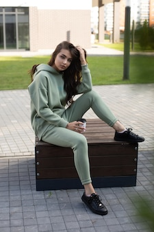 Foto conservada em estoque de uma jovem encantadora com capuz verde-oliva e corredores, sentado em um banco com uma xícara de café na rua.